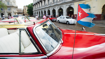 Classic American car in Havanna with Cuban flag